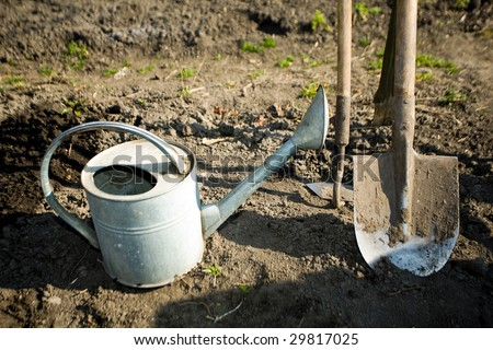 A watering can, a  spade and a  mattock on the ground in a peasant's kitchen garden
