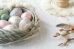 a wattle rattan basket with self colored eggs on a ivory table, decorated with a macrame doily and pussy willow twigs