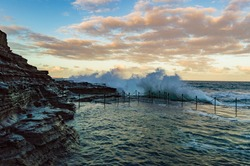 A wave breaking on the Bogey Hole in Newcastle Australia. This convict created swimming hole is popular place to cool off in Newcastle, Australia.