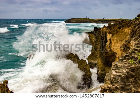 A wave crashes against a rocky shore on the south shore of Kauai just east of Poipu, Hawaii #1452807617