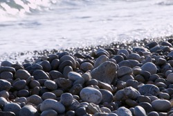 A wave meets the pebbles in a curve and large pebbles caught by sunlight highlights their shapes. Bokeh sparkle from glistening wet pebbles echoes the curve of the sea. Uplifting and grounding at once