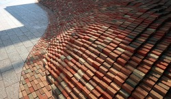 A wave-shaped sculpture made of bricks