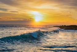 A wave with the sunset in Hawaii.