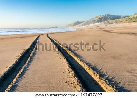 A 4WD car track in a wild beach sand going towards an endless infinite horizon at the Chilean coastline in Topocalma beach, Puertecillo, Chile #1167477697