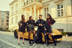A wealthy man in a golden car surrounded by women. The man is all in gold, is popular with girls. Friends came to a party at the cottage. A man surrounds women.