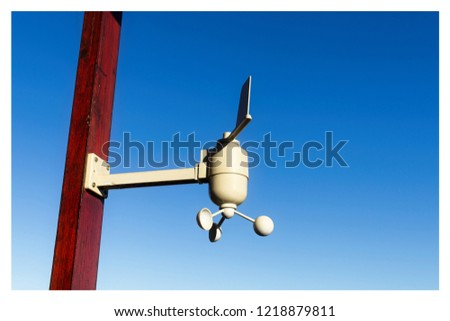 A weather measuring device attached to a wooden pole with a blue sky background. This image can use to represent the concept of meteorology or weather forecasting.