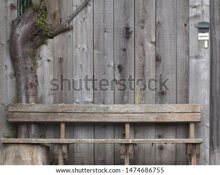 """A weathered bench in front of a weathered fence with a tree growing through it. A sign that says """"ARTISTE"""". #1474686755"""