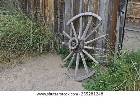 A weathered, broken old wagon wheel leaning against a barn on a farm in Colorado.