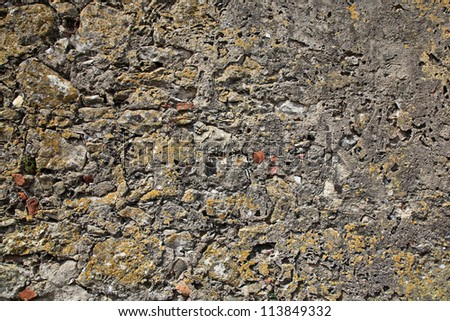 A weathered concrete rubble and stone wall for background use.