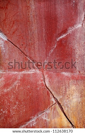 A weathered red stone wall with cracks and crevices for textural background.