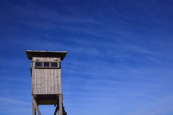 A weathered wooden stand for hunters stands on wooden posts and has a narrow window. The high stand is at the bottom of the picture against a blue sky with clouds in Bavaria