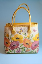 A webbing bag with flower decoupage theme.