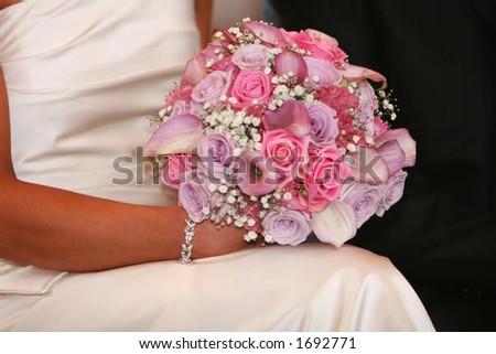 A wedding bracelet and bouquet,, bride sitting with bouquet,, focus on silver bracelet