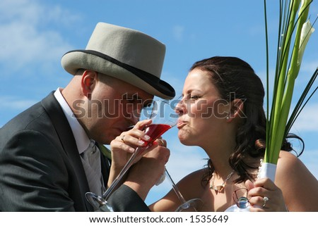 A wedding, bride and groom toasting in bubbly wine outside in sunshine, against a blue sky