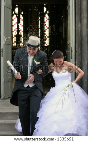 A wedding, bride and groom walking out of church after ceremony into a rain of rice from guests
