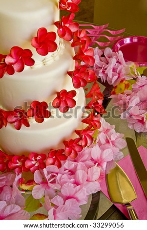 stock photo A wedding cake with red flowers surrounded by pink flowers