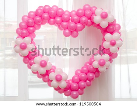 a wedding decoration - many pink balloons in a heart shape - stock photo