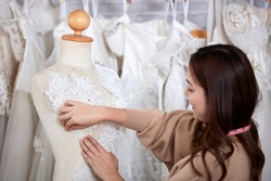 A wedding dress rental shop owner standing working with a mannequin and equipment. Women dressmaker in her bridal boutique. Small business and marriage concept.