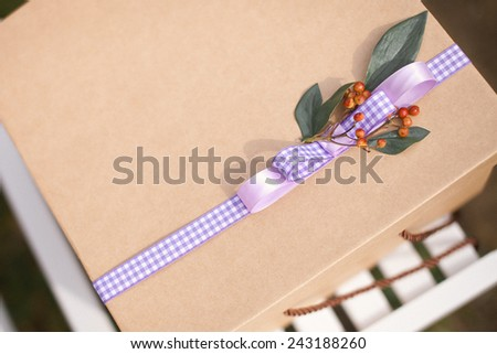 A wedding gift. Simple craft box with checkered violet wrapper stripe with leaves and cow berry on a wedding chair