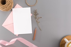 A wedding mock up concept. Wedding Invitation, envelopes, cards Papers on grey background with ribbon and decoration. Top view, flat lay, copy space