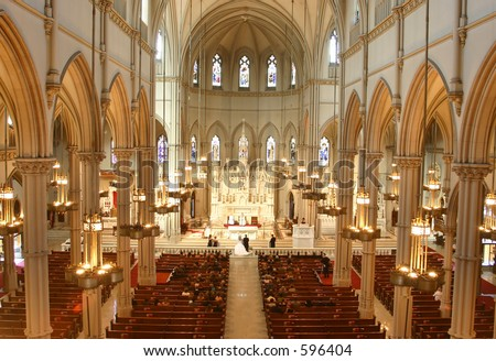 A wedding takes place inside an ornate church.