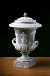 A Wedgwood lilac Jasper two-handled, Campagna urn and cover with a pair of early 20th century Wedgwood Etruria, two-handled classical, porcelain urns. Photographed on wood with a black background.