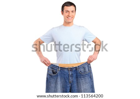 A weight loss male showing his old jeans isolated on white