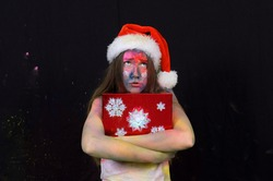 A weird teenage girl wears a Santa Claus hat at  Christmas time. Her clothes and face are filthy  from power paint. She holds a large red present in her hands.