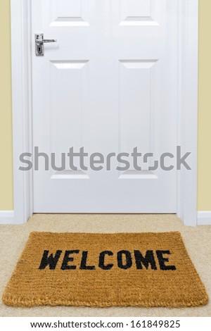 A Welcome doormat in front of a door.