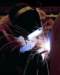 A welder welding the top on a pressure vessel.