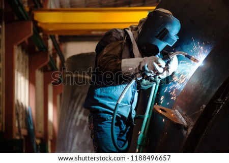 A welder worker is a metalworker. Heavy industry welder worker in protective mask hand holding arc welding torch working on metal construction