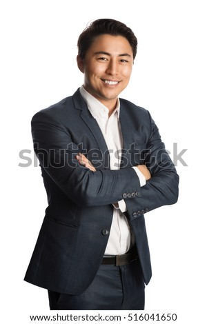 A well dressed businessman in a blue suit and white shirt, standing against a white background smiling towards camera.