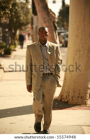a well dressed male model walks down a city sidewalk as if he is walking down a cat walk at a fashion show