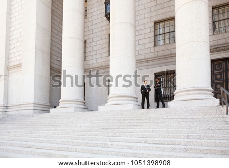 A well dressed man and woman converse on the steps of a legal or municipal building. Could be business or legal professionals or lawyer and client.