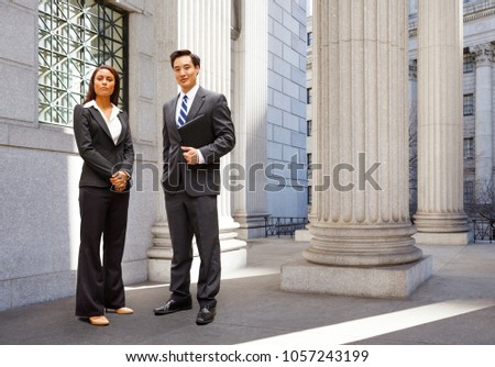 A well dressed man and woman stand among the columns of a legal or municipal building. Could be politicians, business or legal professionals. #1057243199
