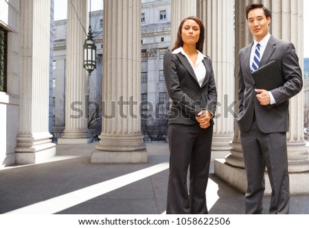 A well dressed man and woman stand among the columns of a legal or municipal building. Could be politicians, business or legal professionals. #1058622506
