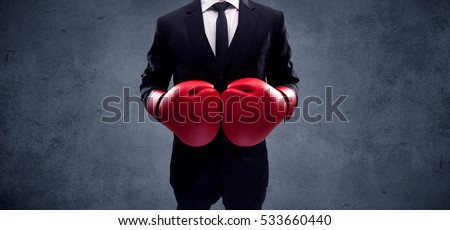A well dressed sales person standing with red boxing gloves on his hand in front of urban grey wall background concept. #533660440