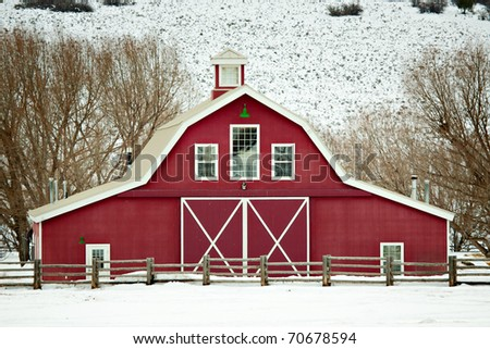 A well-kept, classic red barn in a rural winter setting in Utah, USA.