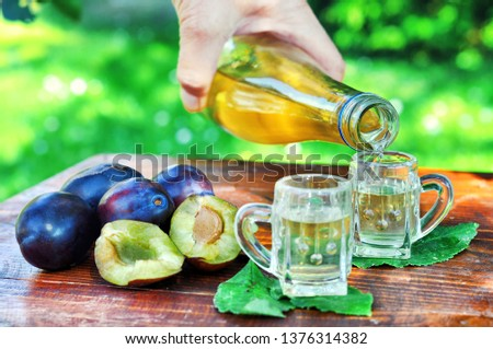 A well-known brandy rakia slivovitz in shot glasses with plums on wooden table in orchard.  Traditional Serbian brand alcoholic drink of organic production.Human hand pouring a well-known brandy rakia #1376314382