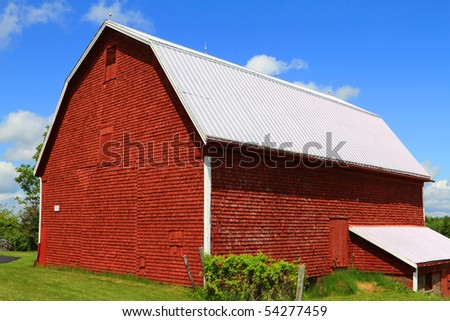 A well maintained red barn in summer