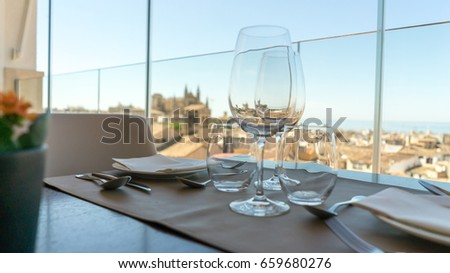 A well set-table with sea views and a orange flower.  #659680276
