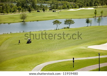 A well-tended golf green with sand traps, golf carts and players in Florida.
