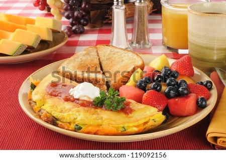 A Western Omelet with fresh fruit and berries for breakfast