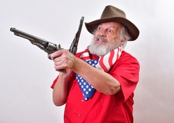 A Western rancher wearing a patriotic bandana has two pistols with one ready to fire and the other being cocked.  A mean looking old man with a viscous snarl and two pistols.