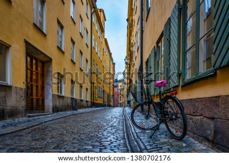 A wet and glistening cobblestone street after a rainfall, surrounded by colorful houses in Stockholm's old town area called Gamla Stan