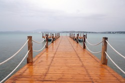 A wet wooden pier with rope railings extending into the sea on a rainy day