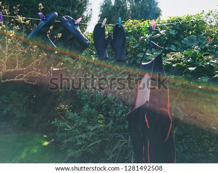 A wetsuit, wetsuit boots and gloves hang on a washing line drying in the sun with a rainbow across the picture. #1281492508