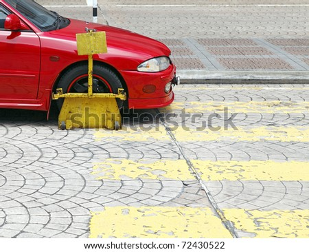 A wheel clamp on an illegally parked car at a pedestrian crossing.