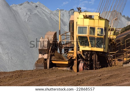 A wheel digger used to excavate minerals at a mine in front of a huge heap of iron ore in action