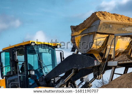 A wheel loader loads sand into a silo. Special construction equipment for earthmoving and handling operations. Foto d'archivio ©